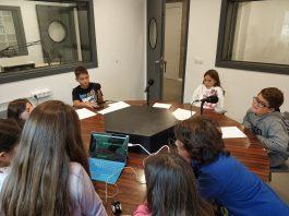 Nens i nenes de 4rt de primària de La Serreta, de la classe de les Aranyes Tigre, als estudis de Ràdio Santepdor gravant El Gronxador