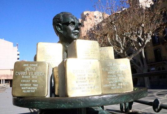 Les llambordes Stolpersteine de Manresa amb una escultura de l'escriptor Joaquim Amat-Pinella.